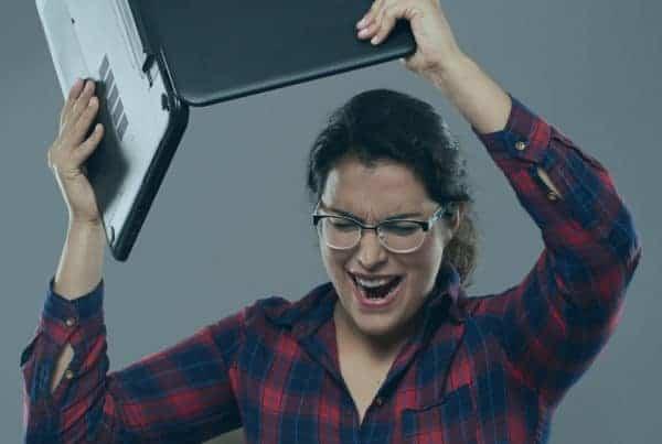 young woman angry smashing laptop